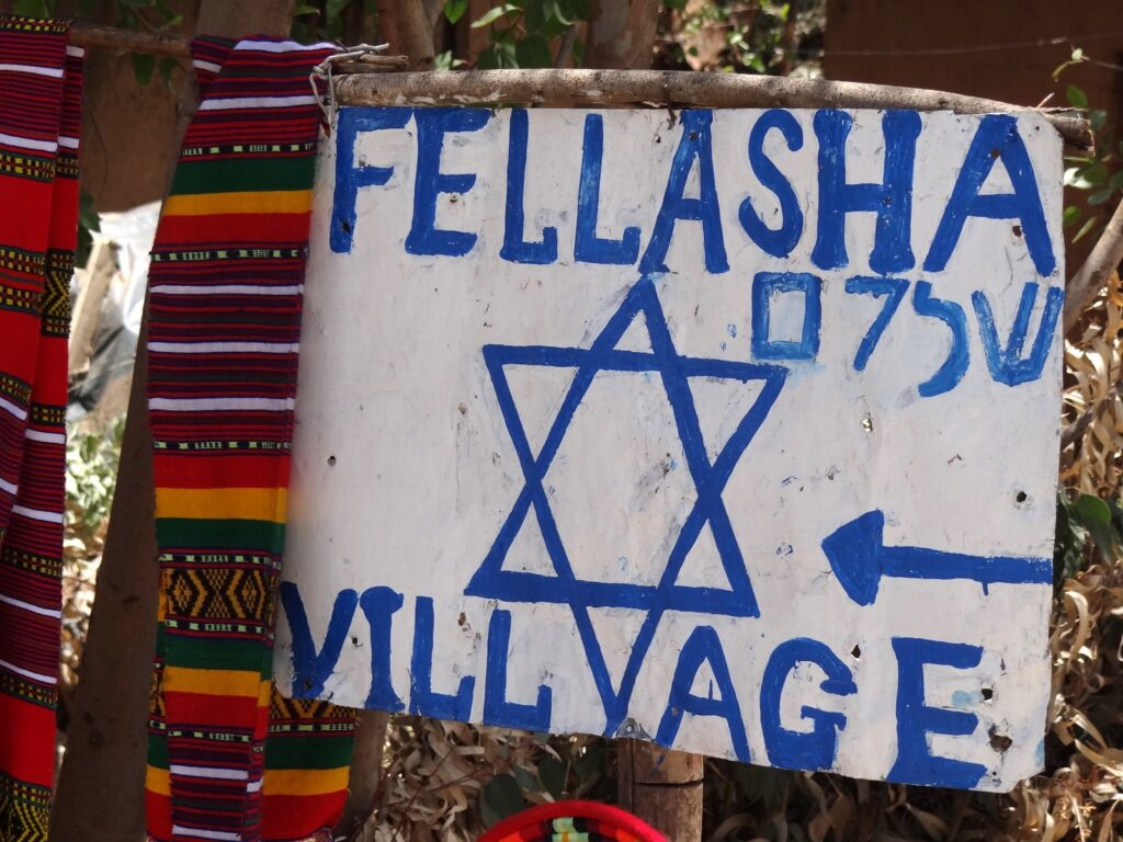 A sign directing tourists to the historical Jewish Village of Wolleka